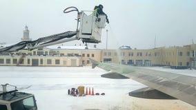Lotnisko personel wykonuje lodowacenia traktowanie samolot zbiory
