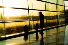 Lotnisko, sylwetka ojciec z dzieciakami, zamazani samoloty za wysokimi okno, Dublin Irlandia, wsch?d s?o?ca zdjęcia royalty free