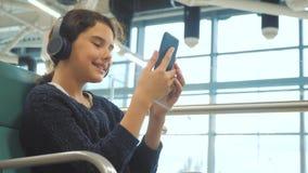 Lotniskowy czekanie sali pokój dla lota styl życia samolotem m?oda szcz??liwa nastoletnia dziewczyna s?ucha muzyka dalej w he?mof zbiory wideo