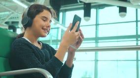 Lotniskowy czekanie sali pokój dla styl życia lota samolotem m?oda szcz??liwa nastoletnia dziewczyna s?ucha muzyka dalej w he?mof zdjęcie wideo