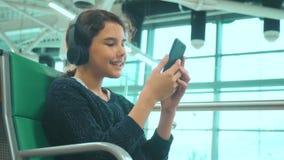 Lotniskowy czekanie sali pok?j dla lota p?askim styl ?ycia Młoda szczęśliwa nastoletnia dziewczyna słucha muzyka w hełmofonach zbiory