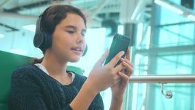 Lotniskowy czekanie sali pok?j dla lota samolotem młodego szczęśliwego styl życia nastoletnia dziewczyna słucha muzyka dalej w he zdjęcie wideo