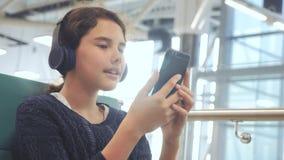 Lotniskowy czekanie sali pok?j dla lota samolotem młody szczęśliwy nastoletni dziewczyny styl życia w hełmofonach słucha muzyka d zdjęcie wideo