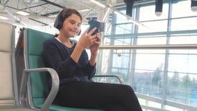 Lotniskowy czekanie sali pok?j dla lota samolotem m?oda szcz??liwa nastoletnia dziewczyna s?ucha muzyka dalej w he?mofonach zbiory