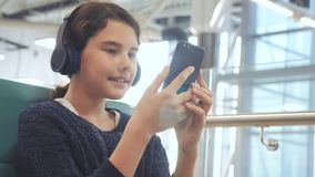 Lotniskowy czekanie sali pok?j dla lota samolotem m?oda szcz??liwa nastoletnia dziewczyna s?ucha muzyka dalej w he?mofonach zdjęcie wideo