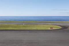 Lotniskowy pas startowy blisko do oceanu z liniami i ogrodzeniem Zdjęcie Stock