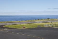 Lotniskowy pas startowy blisko do oceanu z liniami i ogrodzeniem Zdjęcia Royalty Free