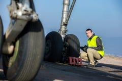 Lotniskowy pracownik sprawdza podwozie Zdjęcia Royalty Free