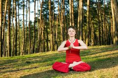 In lotos pose. A young pretty woman sitting in lotos pose on the forest background Royalty Free Stock Photography