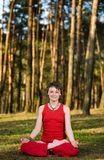 In lotos pose. A young pretty woman sitting in lotos pose on the forest background Stock Images