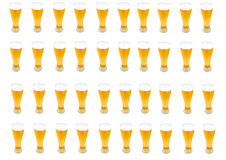 Lots of Beer pints. In a row with frothy heads isolated on white Royalty Free Stock Photography