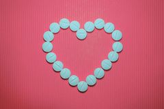 Lots of blue smooth convex tablets with dividing strip on pink striped background, in the form of heart. Top view stock image