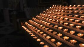 Candles burn near the altar, church ritual. Lots of candles with shallow depth. Small candles. lighted candles on table in Catholic Church