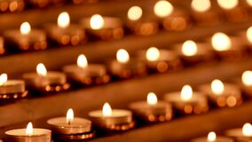 Lots of candles with shallow depth. Small candles on table in Catholic Church. stock video footage
