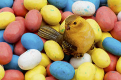 Lots of candy Easter Eggs surround a small bird. Royalty Free Stock Photos