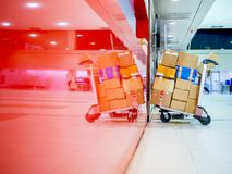 Lots of cardboards boxes on airport luggage cart in airport terminal royalty free stock images