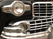 Lots of Chrome. The chrome front grill and headlight of a classic car royalty free stock image