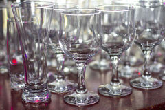 Lots of clean empty glasses of drinks on the bar in a nightclub. Glare and reflections on the glasses in the dark Royalty Free Stock Image