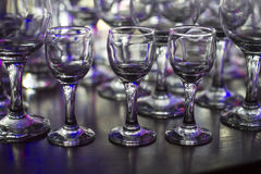 Lots of clean empty glasses of drinks on the bar in a nightclub. Glare and reflections on the glasses in the dark Stock Photos