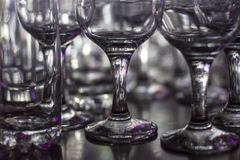 Lots of clean empty glasses of drinks on the bar in a nightclub. Glare and reflections on the glasses in the dark Royalty Free Stock Photos