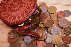 Lots of coins lying around leather wallet. On the table Stock Photo