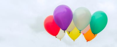 Lots of colorful balloons on the blue sky, concept of love in summer and valentine, wedding honeymoon - Panoramic banner. Royalty Free Stock Photography