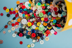 Lots of Colorful Buttons. Beautiful, colorful buttons in a yellow polka dot bowl spilling out onto a blue wooden background Stock Photos