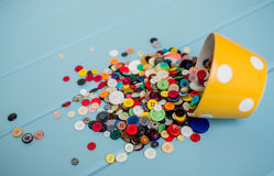Lots of Colorful Buttons. Beautiful, colorful buttons in a yellow polka dot bowl spilling out onto a blue wooden background Royalty Free Stock Photography