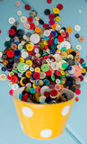 Lots of Colorful Buttons. Beautiful, colorful buttons in a yellow polka dot bowl spilling out onto a blue wooden background Stock Images