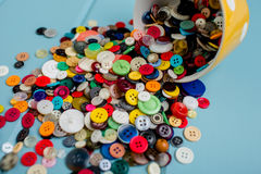 Lots of Colorful Buttons. Beautiful, colorful buttons in a yellow polka dot bowl spilling out onto a blue wooden background Stock Image