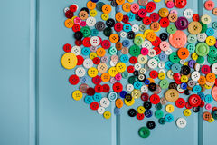 Lots of Colorful Buttons on Blue Wood. Beautiful, colorful buttons on a blue wooden background Stock Photos