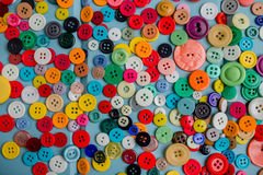 Lots of Colorful Buttons on Blue Wood. Beautiful, colorful buttons on a blue wooden background Royalty Free Stock Photos