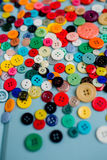 Lots of Colorful Buttons on Blue Wood. Beautiful, colorful buttons on a blue wooden background Stock Photography