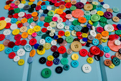 Lots of Colorful Buttons on Blue Wood. Beautiful, colorful buttons on a blue wooden background Royalty Free Stock Photo