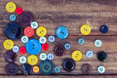 Lots of colorful buttons for clothes on wooden background. Royalty Free Stock Photo