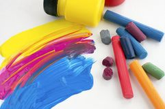 Lots of colorful crayons, tube of yellow paint. Brush strokes. Lots of colorful crayons, tube of yellow paint. Brush strokes Art supplies stock photo