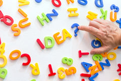 Lots of colorful letters on a table, man forming the word idea Stock Photography