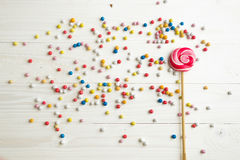 Lots of colorful little candies and lollipop on white wooden bac Royalty Free Stock Photography