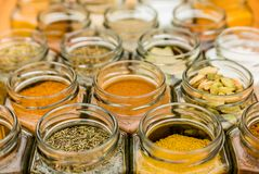 Lots of colorful tasty seasoning spices in glass jars. Many jars of tasty seasoning herbs and spices. Horizontal photo Royalty Free Stock Photography