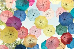 Lots of colorful umbrellas flying in sky over city street during. Summer festival. Fun and happy background concept. Vintage and retro threme Stock Image