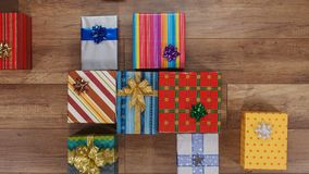 Lots of colorful wrapped presents gather on wooden surface stock video