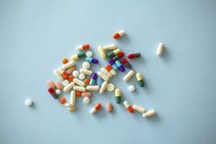 Lots of colourful capsules on blue background. Lots of colourful capsules on  blue background Stock Photo