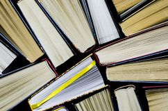 Lots of colourful thick open books stand on a dark background. Ready to read stock image