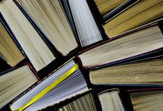 Lots of colourful thick open books stand on a dark background. Ready to read stock images