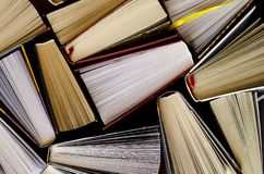 Lots of colourful thick open books stand on a dark background. Ready to read royalty free stock photo