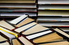 Lots of colourful thick open books stand on a dark background. ready to read. Close-up royalty free stock photography