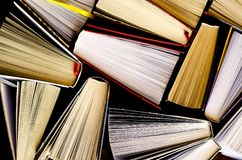 Lots of colourful thick open books stand on a dark background stock photo