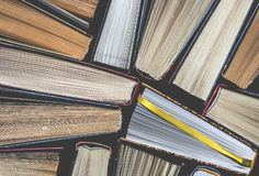Lots of colourful thick open books stand on a dark background. ready to read. Close-up stock image