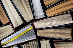 Lots of colourful thick open books stand on a dark background. ready to read. Close-up royalty free stock images