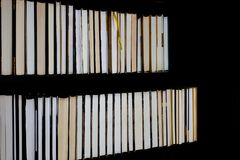 Lots of colourful thick open books stand on a dark background. Ready to read royalty free stock photography